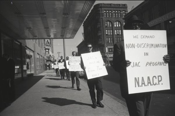 National Association for the Advancement of Colored People (NAACP) picketers outside the Schroeder Hotel where the Apprenticeship meeting was held. A Blatz Beer sign can be seen in the background.