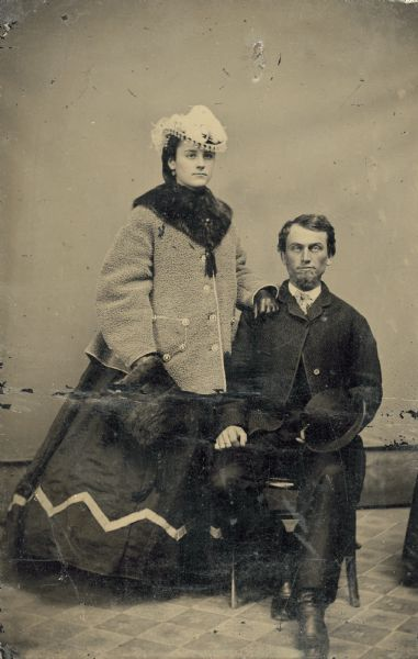 Tintype of Alexander Simplot, sitting, and his wife, standing, who is wearing a fashionable hat and coat and holding a fur muff.
