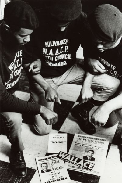 Three members of the National Association for the Advancement of Colored People Youth Council Commandos (Milwaukee) kneel over George Wallace presidential campaign materials. All three young men wear berets and shirts with the name of their organization.
