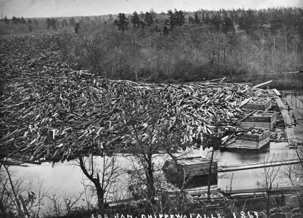 Elevated view from steep shoreline of a log jam of about 150 million feet of logs, stopped at the piers of Pound, Halbert, and Co., which stood in about 40 feet of water. In some places the logs piled up 20 feet above the water.