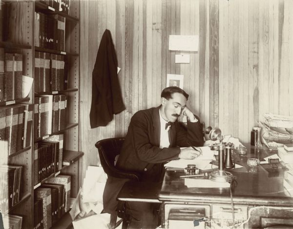 Charles McCarthy writing at his desk in his office.