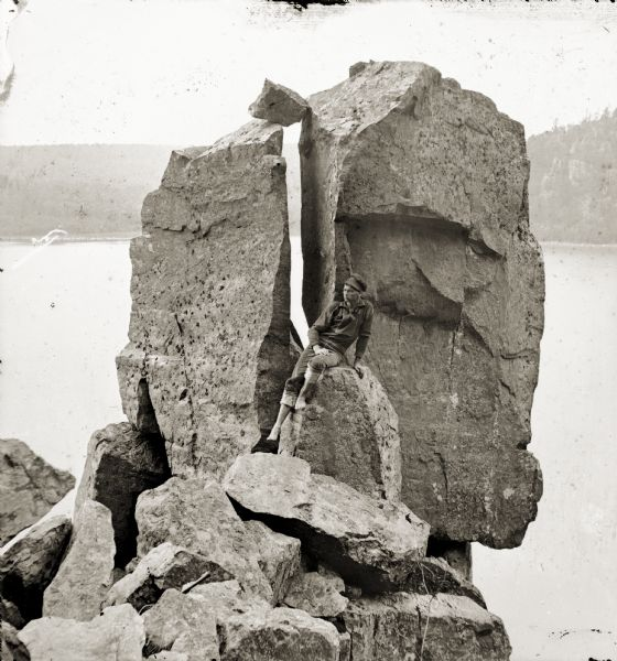 Devil's Lake vicinity; young man seated on rocks in front of Cleft Rock on East Bluff.
