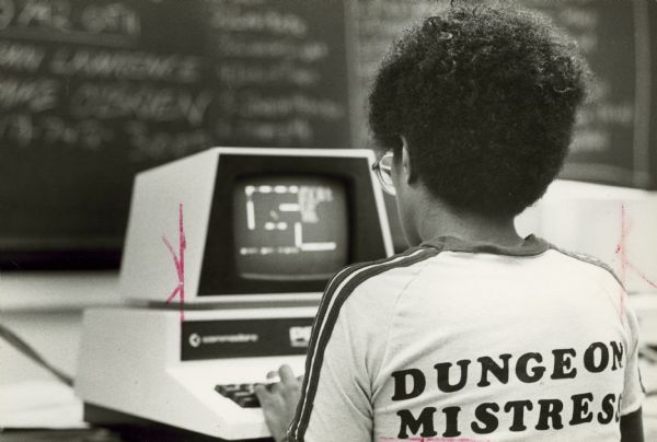 View from behind of a young woman wearing a t-shirt with the title Dungeon Mistress printed on the back while she plays an adventure game on a computer. In the background is a blackboard