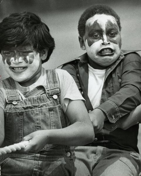 Two boys are in the midst of a game of tug of war. They're dressed in overalls, jeans and t-shirts and are in full KISS makeup. KISS was a rock band which was popular in the 1970's.