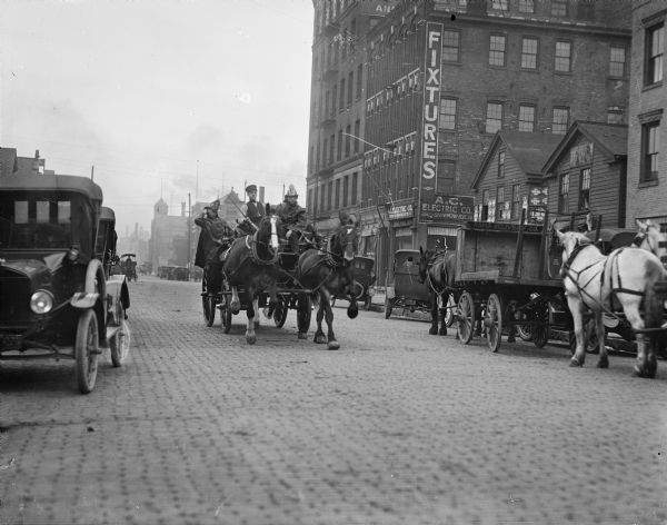 Horse-drawn fire wagon going down a cobblestone street in Milwaukee. The fact that automobiles also appear in the picture suggest that the transition to motor-driven emergency vehicles did not immediately follow the introduction of passenger cars.