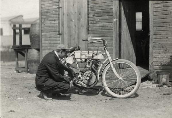 A man crouches down for a close look at a 1905 model Harley-Davidson motorcycle.
