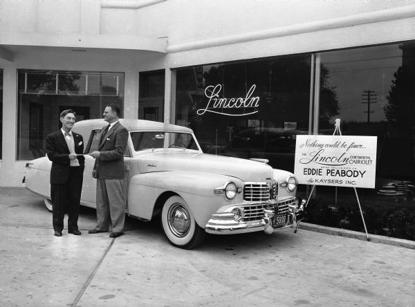"""Eddie Peabody with his new Lincoln Continental, receiving the title from Lucien S. Hanks, general manager of Kayser Motors, Inc., 1501 Monroe Street. Eddie Peabody was known as """"the banjo king"""" in Madison."""