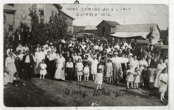 View of a large group of people gathered for a Homecoming celebration. A young woman in the foreground is identified as Daisy Helen Hicken.