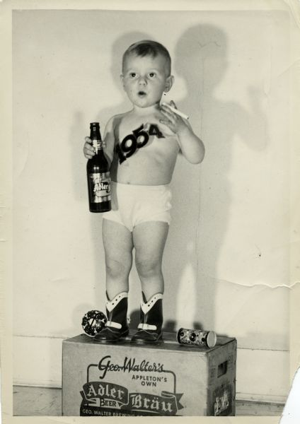 A young Jimmy Clark dressed as Baby New Year for 1954. He stands on top of a case of Adler Bräu wearing cowboy boots, underwear, and a sash reading 1954. He also holds a cigarette and a bottle of Adler Bräu. Two toys lay on the box next to his boots.