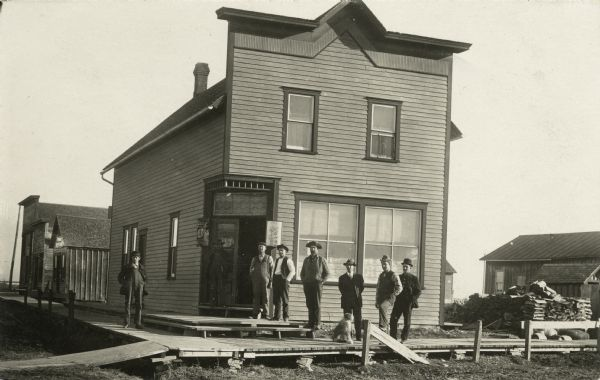 Eight men standing outside a corner tavern. The men are standing on a plank sidewalk with a dog. The is a Blatz Beer sign hanging outside the door.