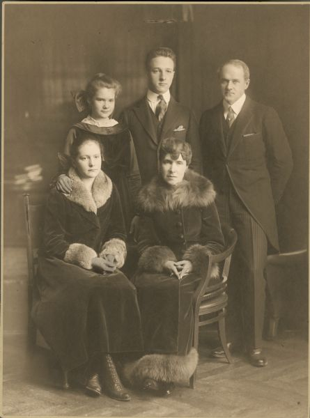 Full-length formal studio portrait in front of a painted backdrop of the family of Harold McCormick and Edith Rockefeller McCormick. From left to right standing are Mathilde McCormick, Fowler McCormick and Harold McCormick. Seated from left to right are Muriel McCormick and Edith, both wearing long coats.