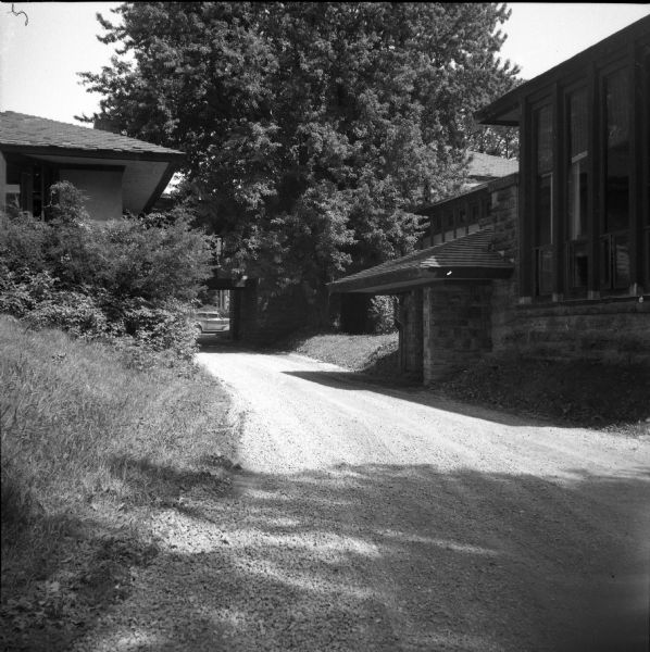 Exterior view from driveway of the entry to the Hillside Playhouse, with a large tree obscuring part of the building in the background.