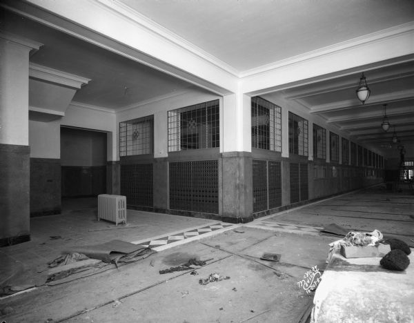 Interior view of first floor lobby with construction debris and some tile work completed on the floor. In the background a man is standing on a ladder near light fixtures hanging from the ceiling.
