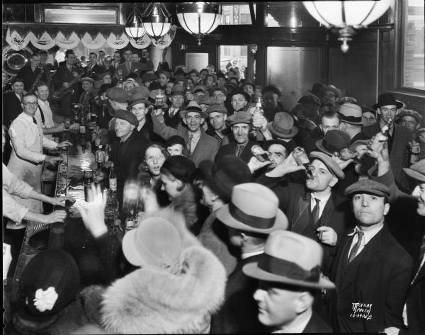 Slightly elevated view of crowd in the Fauerbach Brewery tavern at 651 Williamson Street, with men and women drinking and toasting and celebrating the end of Prohibition. A small band plays in the background.