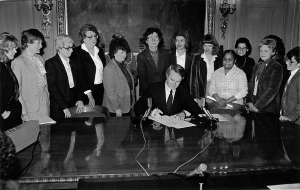 Governor Tony Earl at the signing of the executive order creating the Wisconsin Women's Council. At the end of the remarks he invites women from the legislature and his administration to join him for the signing.  Pictured from left to right: 1. Sen. Susan Engeleiter 2. [not identified] 3. Eileen Mershart (Deputy Secretary DOR) 4. Doris Hanson (DOA Secretary) 5. Rep. Barb Gronemus 6. Rep. Mary Lou Munts 7. Rep. Sharon Metz 8. Rep. Barb Ulichny 9. Rep. Marcia P. Coggs 10. Linda Reivitz (DHSS Secretary) 11. Rep. Lolita Schneiders 12. Roberta Gassman (Policy Advisor Governor's Office)