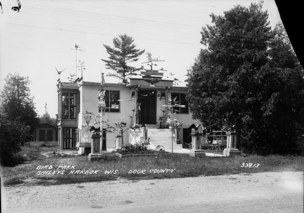 House built by Albert Zahn, Sr. He carved figures of angels, animals, and birds, and after his wife painted them, he mounted them on pillars in the yard. A dog is lying in the yard near the foundation of the house on the left.