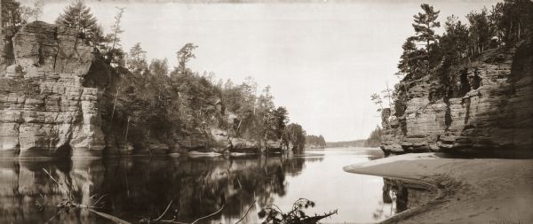 "Panoramic view from shoreline of the Wisconsin River in the Wisconsin Dells. A sandy beach area is on the right, and rock formations are on both sides of the river. In the lower right hand corner are the words ""JAWS OF THE WISCONSIN DELLS. Copyright 1894. by H.H. Bennett."""