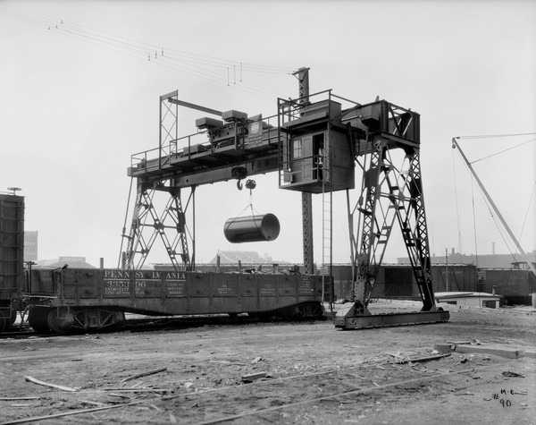 "Gantry crane hoisting a large cylindrical object next to a railroad car. A man is standing in an open doorway in the operating room of the crane. The sign on the crane reads: Milwaukee Electric Crane & Mfg. Corp."" In the far background is the top of a steel bridge, and industrial buildings. One building has a sign on the roof for: ""Knickerbocker Masons Supply Co."""
