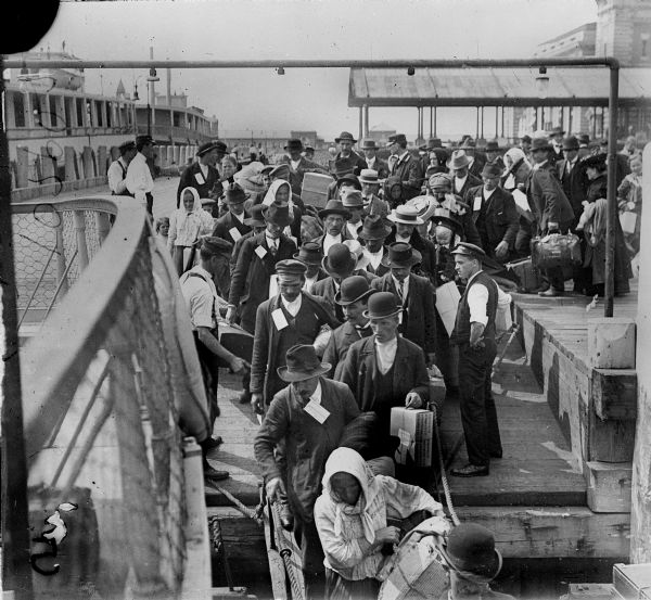 Elevated view from railing of immigrants boarding a ferry to depart Ellis Island.