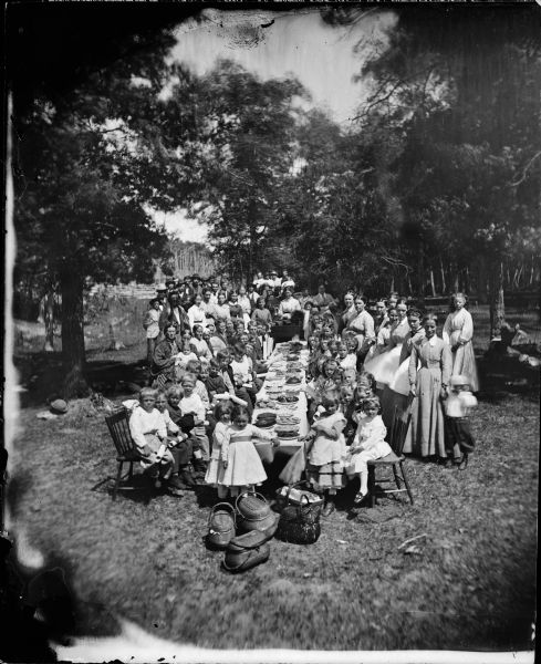 Slightly elevated view of a large, multi-generational Norwegian family and friends gathered for a picnic celebration. In the foreground are picnic baskets on the ground at the end of a long table laden with plates of food. Children holding diplomas are seated in chairs along the side of the table. Adults are posed around the table. A woman holding a bell sits behind another table stacked with books in the center of the group. Women and men stand around the sides.