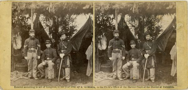 Stereograph of three U.S. Army soldiers in front of tents in camp under a framework of branches.