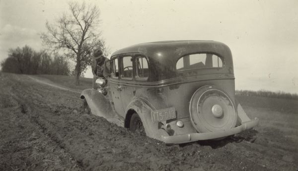 View from rear left of a car belonging to a United States Resettlement Administration field worker stuck in a muddy road. A man stands at the front of the vehicle.