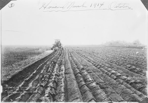 View of furrowed ground in Horicon Marsh and men on a tractor in the process of plowing a drained portion of the marsh.