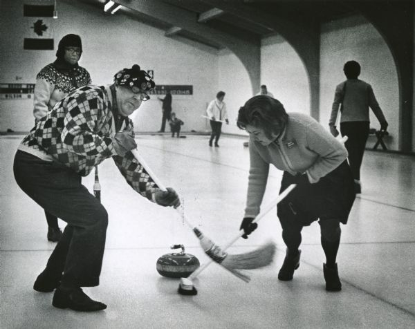 L.J. Brodd and Mrs. Robert Rasche, both of Glendale, sweep ahead of the stone during a match as part of the 21st Annual Milwaukee Mixed Bonspiel. Mrs. Jane Brodd watches in the background.
