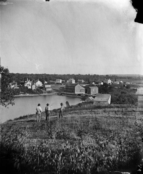 Elevated view from hill of Clinton, now Rockdale. Three men are in the middle distance, looking east across Koshonong Creek towards a mill dam, bridge and carding mill.