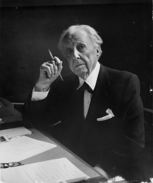 Portrait of Frank Lloyd Wright seated at a desk.