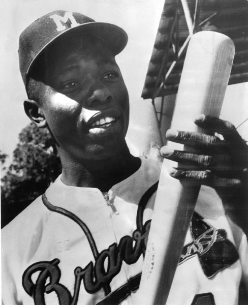 Outdoor portrait of Henry Aaron in a Milwaukee Braves uniform holding a baseball bat.