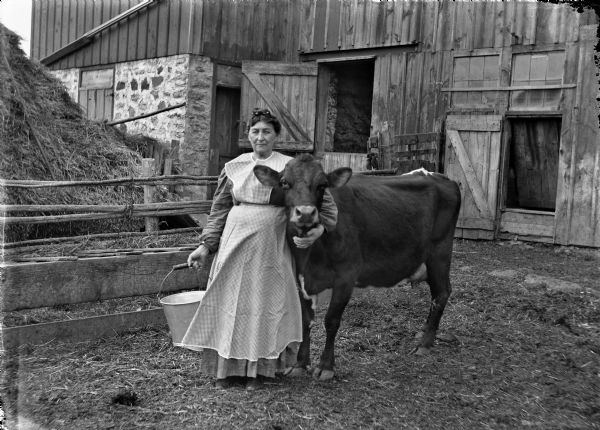 Grandma Martha (Goetsch) Buelke posed in front of a barn with her favorite cow. She is holding a milking pail.