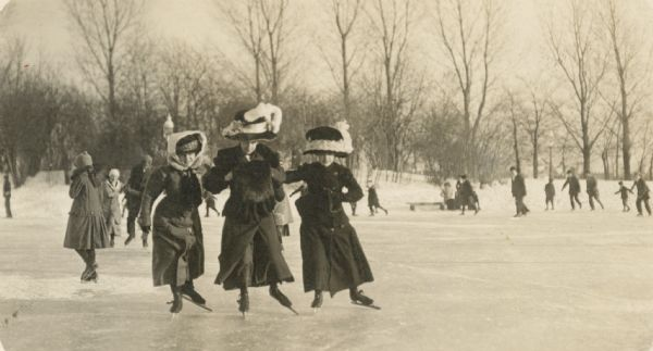Three women wearing large hats ice skating together on a pond.
