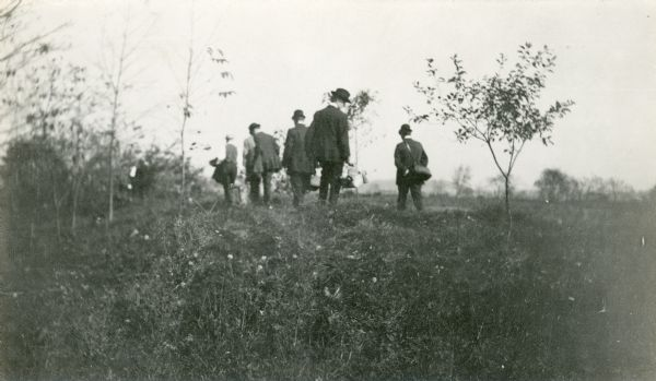 A small group of men, some of them carrying bags, walk in a field among effigy mounds.