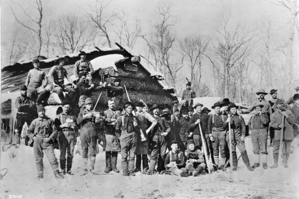 Group portrait of a large logging crew posing outdoors in the snow at their camp in front of a log building. One of the men is playing a fiddle or a violin, and two men are posing with their fists up as if ready to fight. One of the men sitting on the ground in front of the group appears to be holding a dog.