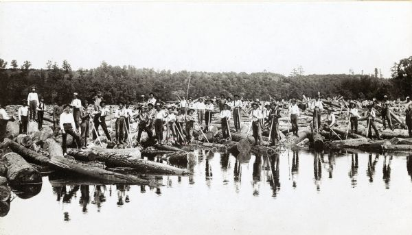 Log driving crew for the Chippewa Lumber & Boom Company. Crew members are in the process of breaking a jam at the Big Eddy. One of the men is carrying a young boy on his shoulder.
