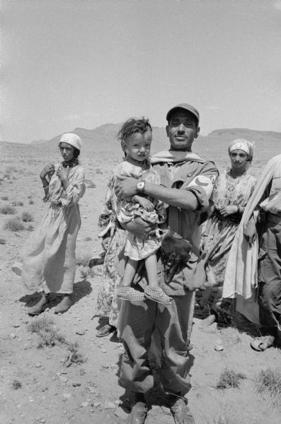 A Red Crescent doctor is holding an Algerian refugee child who survived a French air attack that killed eighteen people. Behind them is a shepherd's daughter who is in training to be an army nurse.