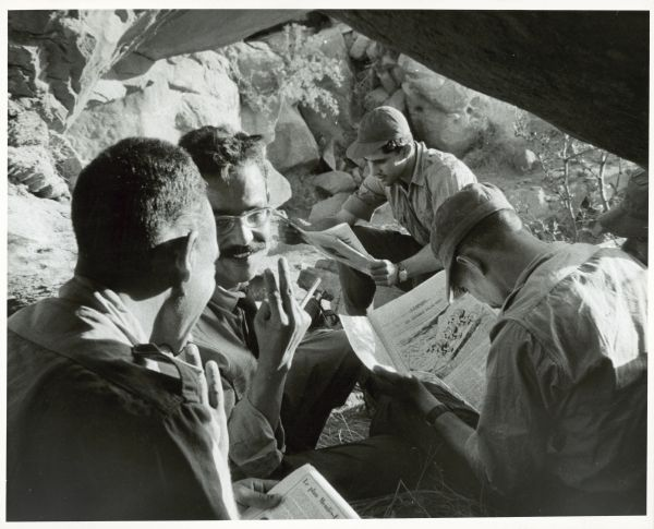 Soldiers sit on the ground outdoors in a rocky area in Algeria reading newspapers.