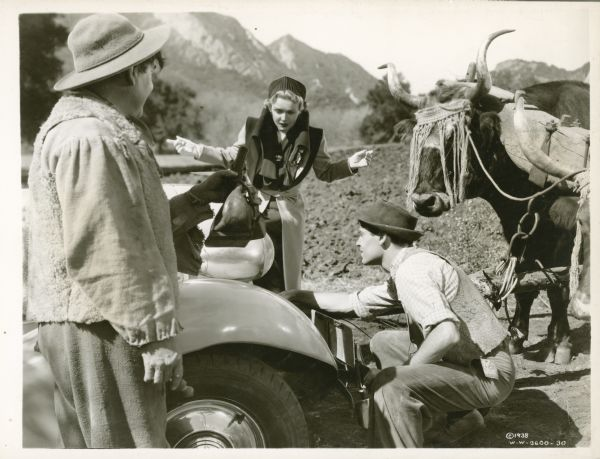 Marco (Henry Fonda) looking at the engine of a car while Norma (Madeleine Carroll) and Luis (Leo Carillo) are looking on. A team of oxen is standing on the right, and a mountain range is in the background.