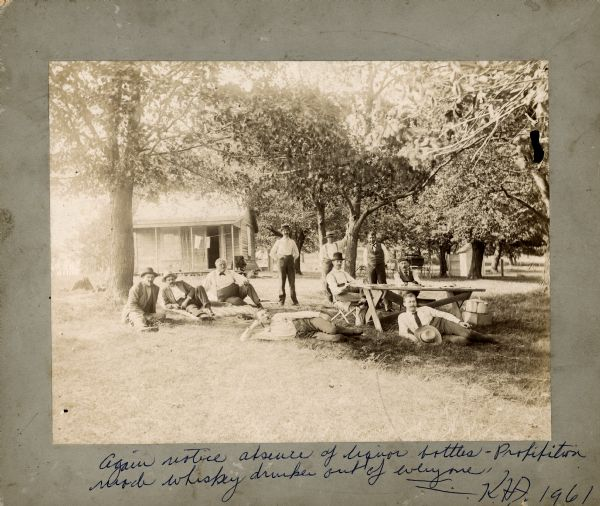 "A group of friends relaxing outdoors. Some are lounging on the grass, two are sitting at a table, and some are standing. Alex Baas is sitting on the grass, third from the left. Philip Fauerbach is standing with his hands in his pockets, third from the right. On the bottom border of the image, Karl Fauerbach wrote the following in blue ink: ""Again notice absence of liquor bottle. Prohibition made whiskey drunks out of everyone."""