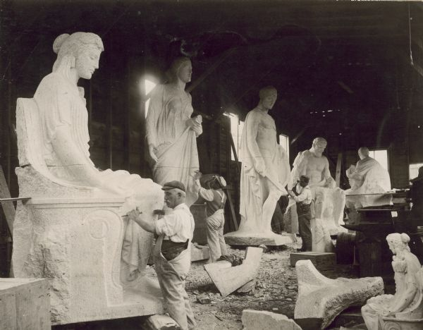 Carvers at work on the Karl Bitter sculpture for the fourth Wisconsin State Capitol (third in Madison). Between 1911 and 1913, a group of stone cutters (many of them Italian) worked on the four figural groups designed for the base of the dome. The figures were first carved near the Milwaukee Road shed and then hoisted into place when completed. Seen here are figures (left to right) faith, abundance, and three elements from strength.