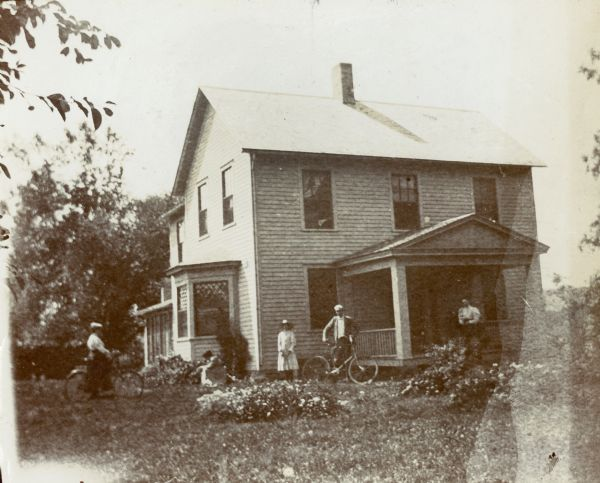 John Lloyd Jones house, near Hillside Home School on Highway 23 across from Taliesin. A man and a woman are standing and holding bicycles, one woman kneels by flowers, one woman stands against the house and another man stands on the porch.