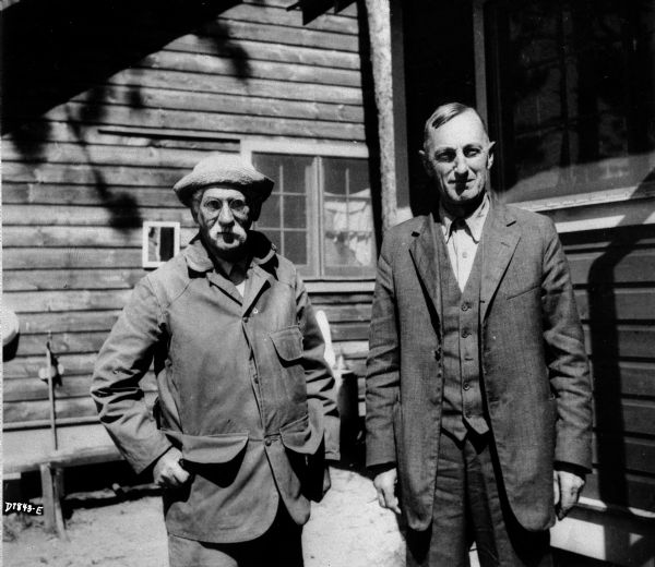 Limnologist Dr. Edward Birge (left) and Professor Chauncey Juday posing together outdoors at what is probably the lake research laboratory in Trout Lake.
