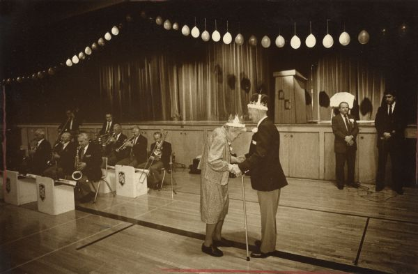 "An elderly couple are dancing together. Both of them are wearing crowns, and the woman is holding a cane. To the left of them a band is playing. Caption reads: ""For some, it had been 40 years since their last prom, for others 50 or more. But the music and the location brought back memories for those who danced to the Grant Krueger Orchestra during the Rotary Club of Mitchell Field's annual Fall Prom at Oak Creek High School Saturday. The prom was open to people age 55 or older who live in St. Francis, Cudahy, South Milwaukee, Oak Creek and Franklin. Ann Marks, 90, of Oak Creek, and Harry Gallau, 72, of Milwaukee, prom queen and king, shared a dance.:"