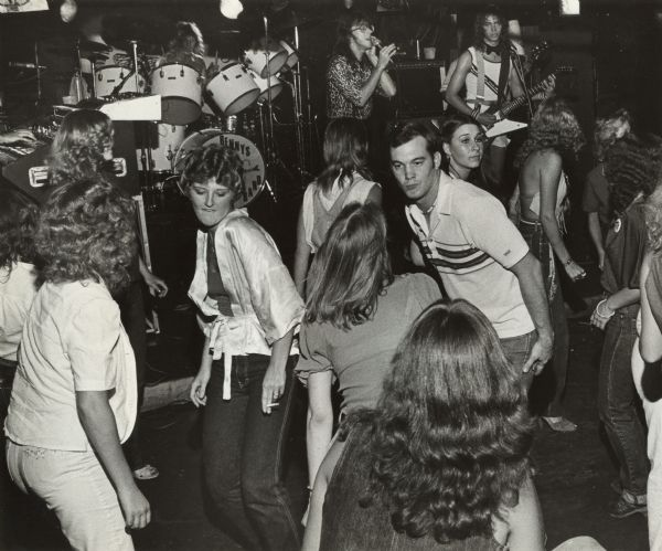 "A group of people are dancing as a band on a stage is playing in the background. Caption reads: ""Rock fans dance to the music of Benny's Basement Band at Fantasy's."""