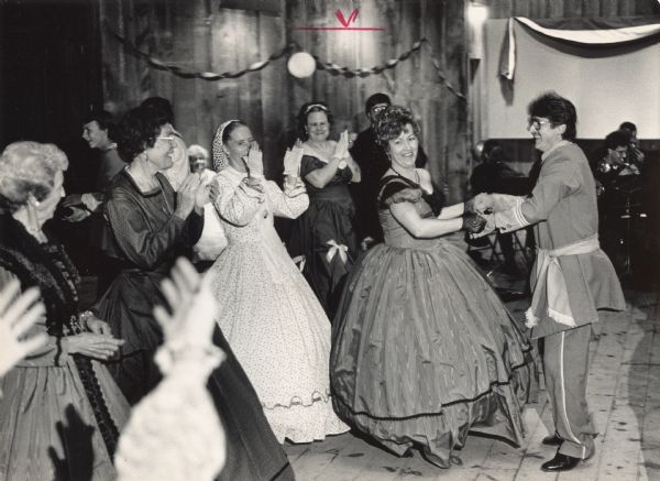 "A costumed couple is dancing while four women in costumes are clapping their hands. Caption reads: ""Dancers strutted their stuff at an '1865 Military Ball' sponsored by Friends of Old World Wisconsin last weekend. The dance for which guests dressed in period costumes was held at the Clausing Barn at Old World Wisconsin, which is near Eagle in southwest Waukesha County. The First Brigade Band played Civil War era music for the dance."""