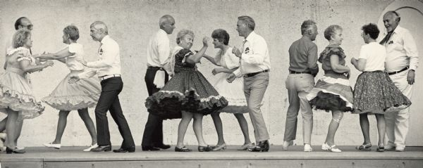 "Three groups of people square dancing on a stage or platform. Caption reads: ""OCONOMOWOC FESTIVAL — The Dousman Derby Dancers went through a square dance routine Saturday during the start of Oconomowoc's Festival Week. Events, which will continue through Sunday, include a history walk beginning at 7 tonight at City Hall and Kids Day events from 9 a.m. to noon Tuesday at Fowler Park."""