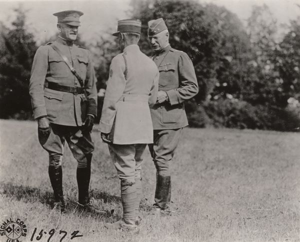 General John Pershing and Major General William George Haan are standing outdoors talking with French Colonel Laucagne.
