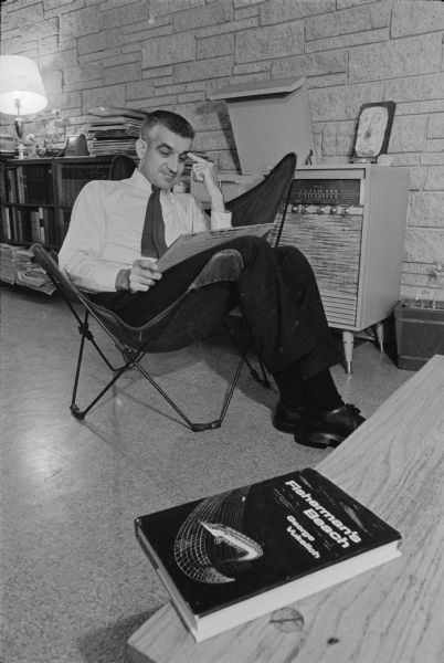 "Radio host and newly published author, George ""Papa Hambone"" Vukelich relaxing at his home on Plymouth Circle. He is sitting in a chair holding an LP copy of Dick Ruedebusch's <i>Meet Mr. Trumpet!!!</i> which is playing on the stereo system in the background. A copy of his first novel, <i>Fisherman's Beach</i> is lying on a table in the foreground. A full bookshelf with a stack of record albums, a lamp, flowers, and a clock are in the background."