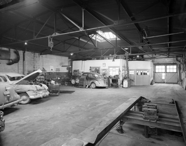 Interior view of the garage. In the foreground is a lift, and in the background on the left is the office, which is under a skylight. Garage doors are to the right of the office. Cars are parked on the left, and one has the hood lifted and tarps have been places around the engine. Another car is near the office, and the front is raised up on ramps. Tools and workbenches are along the wall and on carts, and parts are hanging on the walls.